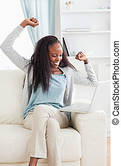 Woman cheering at her laptop