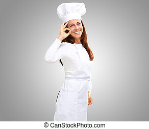 Woman chef gesturing on grey background