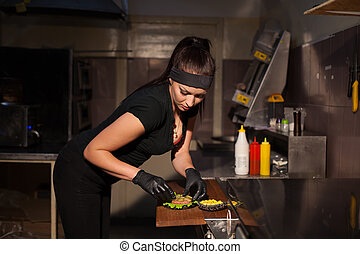 woman chef prepares a burger in the kitchen of the restaurant