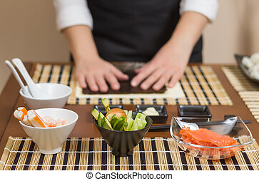 Woman chef ready to prepare japanese sushi rolls, with ...