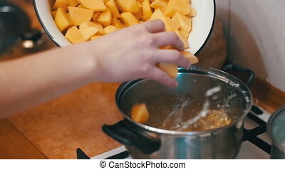 Woman Chef Throws Sliced Potatoes in a Pot to Boil the...