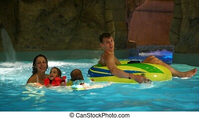 Woman, children and a man on an inflatable boat swim in pool in water park