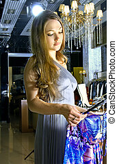 woman chooses a dress in a boutique