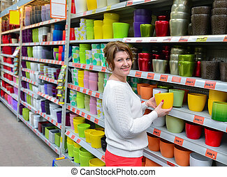 Woman chooses a flower pot in store
