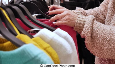 Woman chooses a sweater in a clothing store, sweaters in...