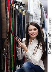 woman  chooses  belt at store