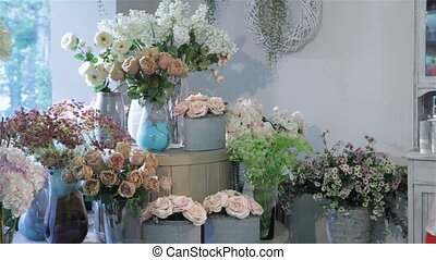 Woman chooses between tea-rose and pink rose at flower shop