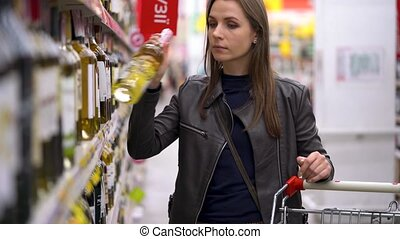 Woman chooses bottle of wine in the supermarket