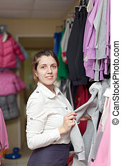 woman chooses casual wear - Young woman chooses casual wear...