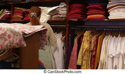 woman chooses clothes in a shop