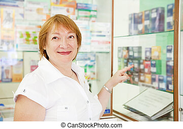 woman chooses contraceptives at pharmacy