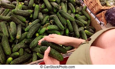 Woman chooses cucumbers at the store counter. view from...