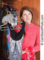 woman chooses dress in wardrobe