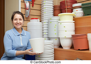 Woman chooses flowerpot in the store - Woman chooses...
