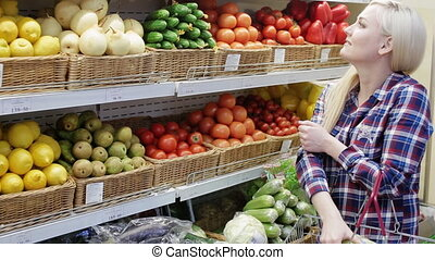woman chooses fruit in a supermarket