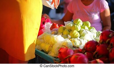 Woman chooses fruits at an open-air market in Koh Samui...