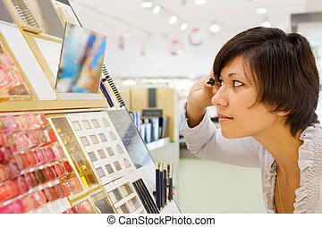 woman chooses mascara at cosmetics shop - Side view of...