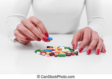 Woman chooses medicine from a handful of different color...