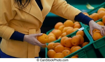 Woman chooses oranges at a supermarket.