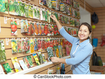 woman chooses packed seeds at store