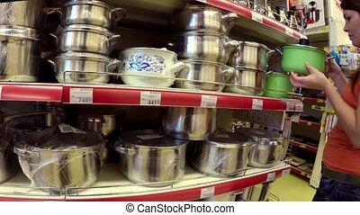 woman chooses pan in shop shelves market - woman chooses pan...