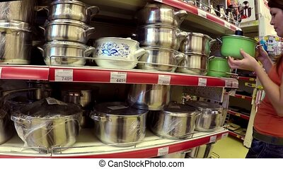 woman chooses pan in shop shelves market - woman chooses pan...
