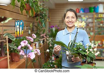 woman chooses Phalaenopsis at flower shop - Happy mature...