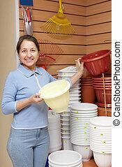 woman chooses plastic flower pot in  store