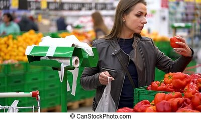 Woman chooses red bell pepper in the supermarket