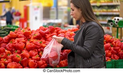 Woman chooses red bell pepper in the supermarket -...