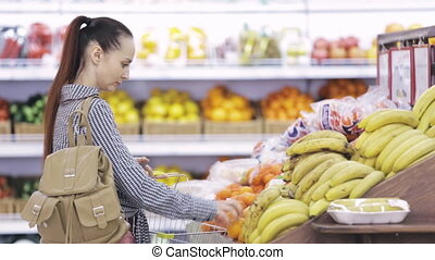 woman chooses ruits in the supermarket