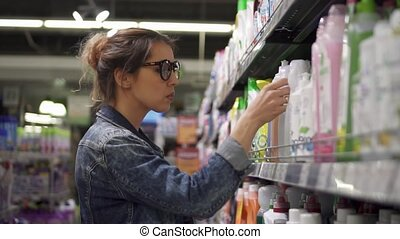 Woman chooses shampoo in the supermarket.