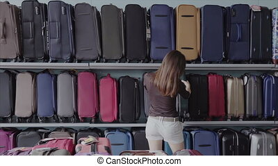 Woman chooses suitcase at shop - woman chooses a suitcase in...