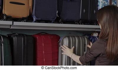 Woman chooses suitcase at shop - Woman shopper chooses...