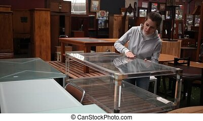 Woman chooses table in furniture store - Woman consumer ...