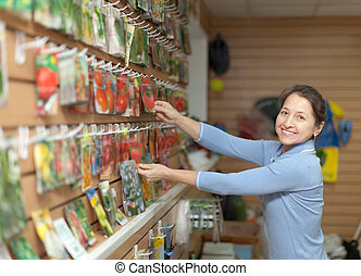 woman chooses the seeds at store