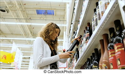 Woman chooses wine in a supermarket, 4K.