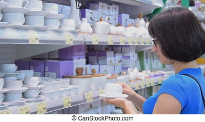 Woman choosing a coffee cup in the store - Young woman...