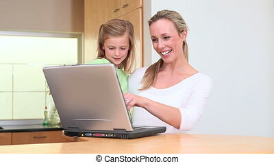 Woman choosing a recipe with her daughter