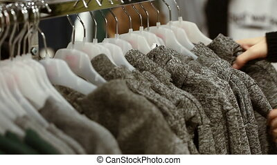 Woman choosing a sweatshirt at shop in shopping centre