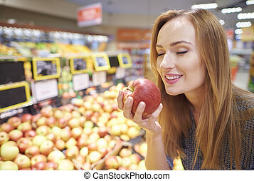 Woman choosing apples from grocery store