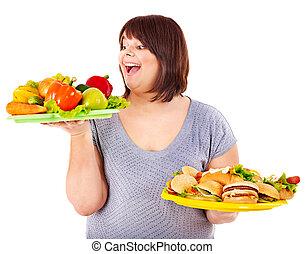 Woman choosing between fruit and hamburger. Isolated.