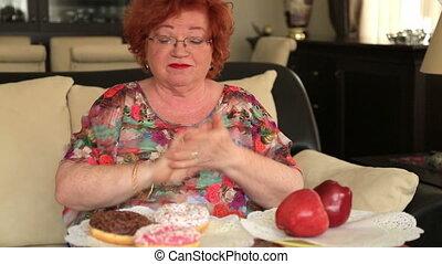 Woman choosing between Sweets and Fruits