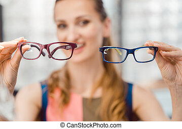 Woman choosing between two models of glasses at optometrist