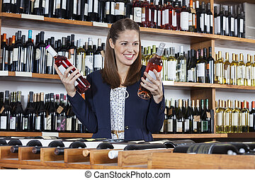 Woman Choosing Between Wine Bottles In Store
