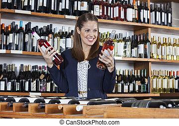 Woman Choosing Between Wine Bottles In Store