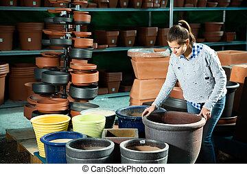 Woman choosing big pot for plants