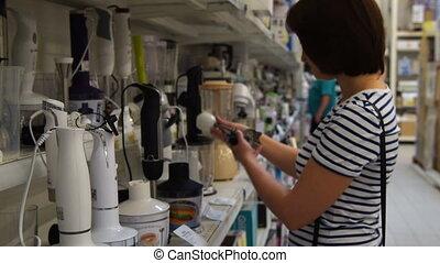 Woman choosing blender in the store