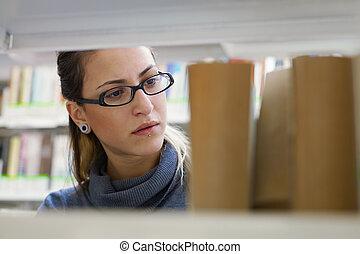 woman choosing book in library