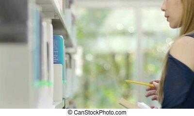 Woman choosing book on shelf